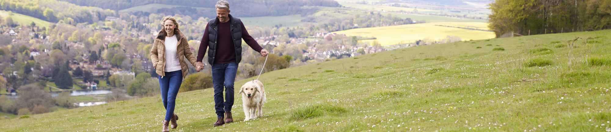 Couple walking dog in countryside - Macdonald Resorts